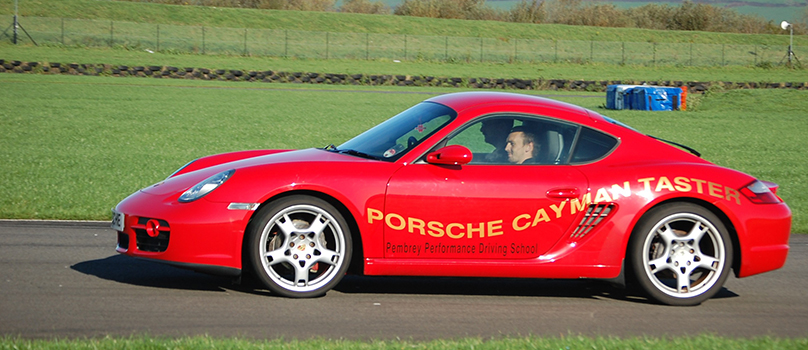 Photo of a customer driving a Porsche Cayman around Pembrey