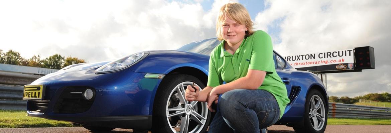 Photo of a junior driver next to a Porsche